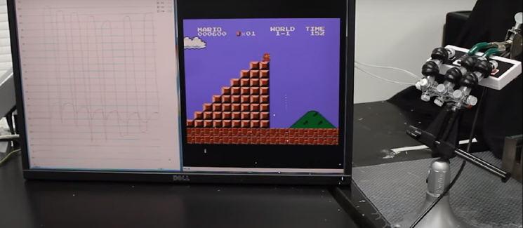 Роботизированная рука играет в видеоигру Super Mario